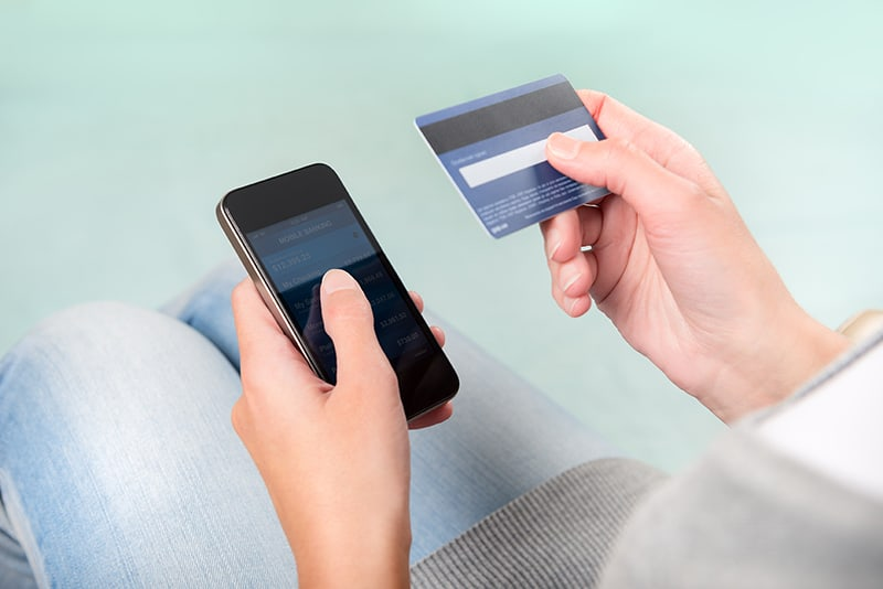 Person using credit card for check cashing app.