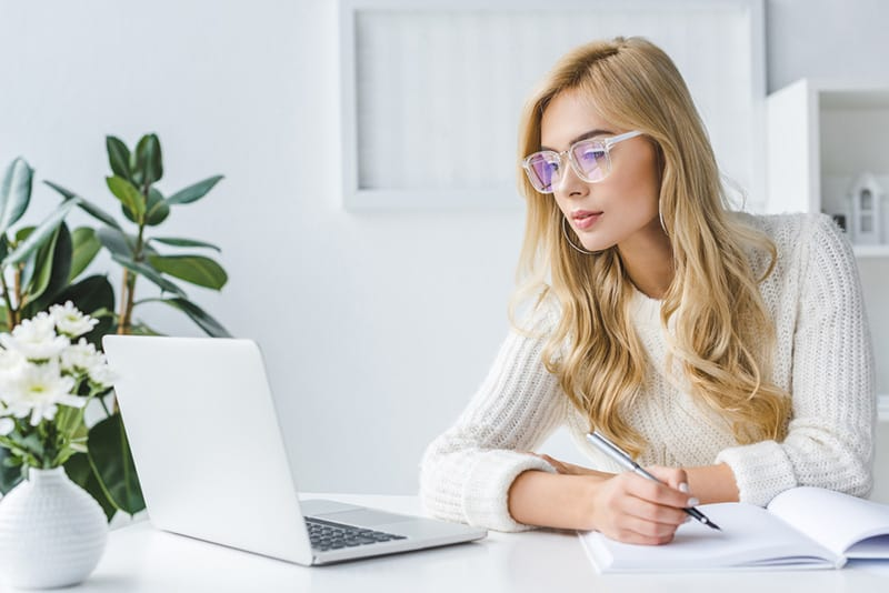 Woman on a laptop looking for the best web hosting.