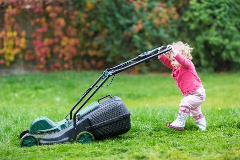 Baby with lawn mower that her parents are going to sell to make extra money from home.